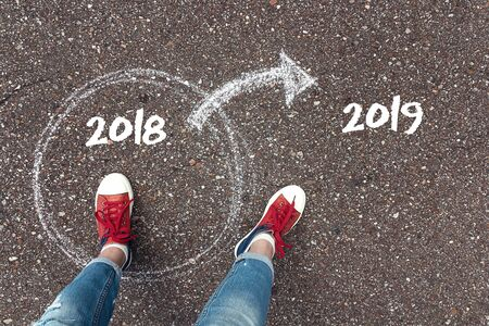 Start new year 2019 and leaving behind old year. Feet  in red sneakers standing inside 2018 year circle and outward arrow on the 2019 year chalky on the asphalt. Concept for success and passing time.