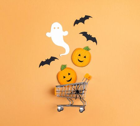 Shopping trolley with decorative pumpkins, ghost, spider and bats on orange backdrop. Flat lay Halloween background. Halloween sale concept.