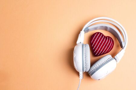 White headphones with red knitted heart and copy space. Top view, flat lay. St. valentine day composition. love music, listen to your heart concept. Stok Fotoğraf