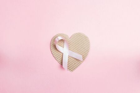 Pink ribbon with cardboard heart on pink background for Breast Cancer Awareness symbol to promote in october month campaign. 版權商用圖片