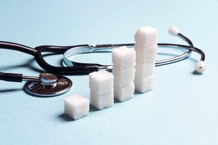 Grafico dello zucchero con lo stetoscopio su fondo blu. Giornata mondiale del diabete, 14 novembre.
