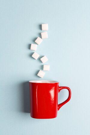Red mug with sugar cubes on a blue background. Sugar addict. Diabetes concept. Standard-Bild