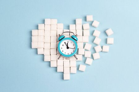 Broken heart made of sugar cubes with alarm clock on a blue background. World diabetes day concept. Stock Photo