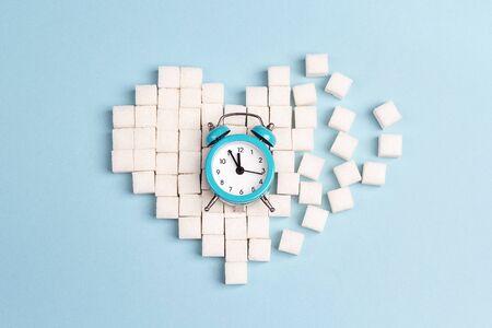 Gebrochenes Herz aus Zuckerwürfeln mit Wecker auf blauem Hintergrund. Konzept des Weltdiabetestages. Standard-Bild