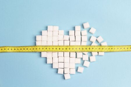 Broken heart made of sugar cubes with measure tape on a blue background. Diabetes, diet and weight loss concept.