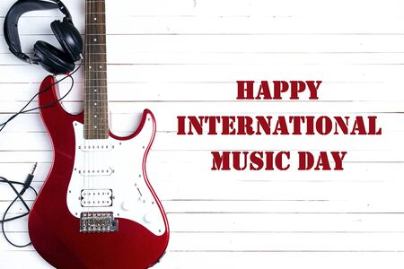 International Music Day background. Electric guitar with headphones on white wooden table.