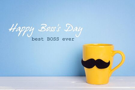 Boss day background with yellow mug with a mustache on blue. Happy boss day concept.