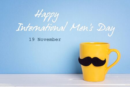 International men's day background with yellow mug with a mustache on blue background. Stock Photo