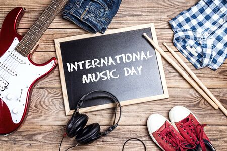 International Music Day background with music equipment, clothes and footwear on wooden table. Stock Photo