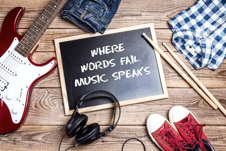 Music background with electric guitar, clothes and footwear on wooden table with phrase Where words fail music speaks. International Music Day background. Stock Photo