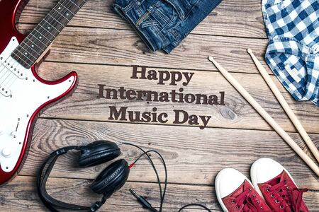 International Music Day background with music equipment, clothes and footwear on wooden background.
