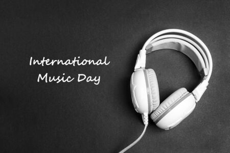 International Music Day background with white headphones on black backgrounds. Top view.