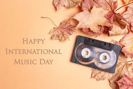 International Music Day background with audio cassette tape and autumn maple leaves.