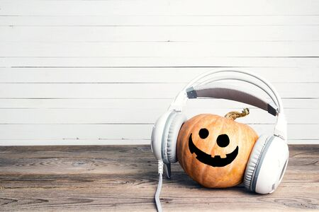 Halloween pumpkin with funny face in headphones.Jack-lantern listen to music on headphones. Copy space for text. 免版税图像