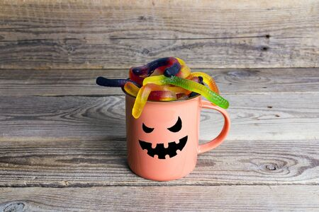 Halloween holiday mug with funny face and candy worms on the old wooden table. Space for text.