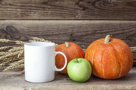 White coffee mug with pumpkins, green  apple and ears of wheat on the old wooden table. Space for text or design.