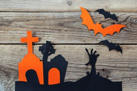Halloween holiday background with cemetery and the zombies hand cut paper on old boards. Space for text.