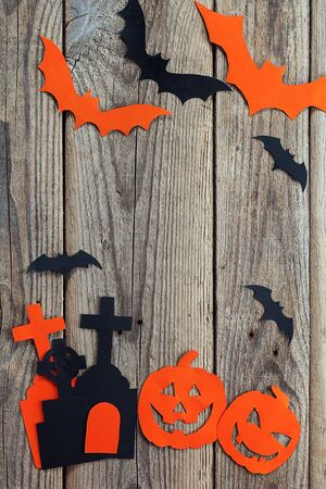 Halloween holiday background with cemetery, pumpkins and bats cut paper on old boards. Space for text. Vertical.