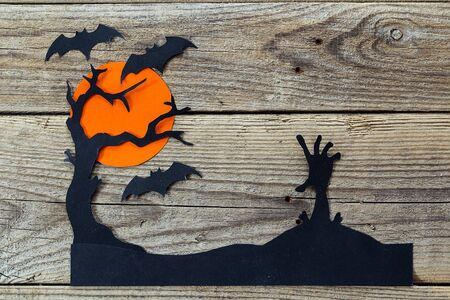 Halloween holiday background with zombies hand, tree and bats cut paper on old boards. Space for text.