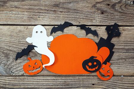 Cloud frame with ghost, pumpkin, bats, headstone cut out of paper. Happy Halloween card. Background of old wooden boards.