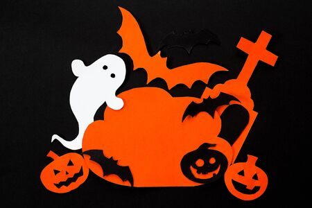 Cloud frame with ghost, pumpkin, bats, headstone cut out of paper. Happy Halloween card. Black background.