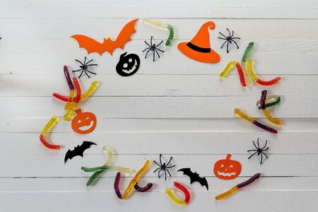 Halloween background with frame of jelly worms, paper pumpkins and decorative spiders. Space for text.
