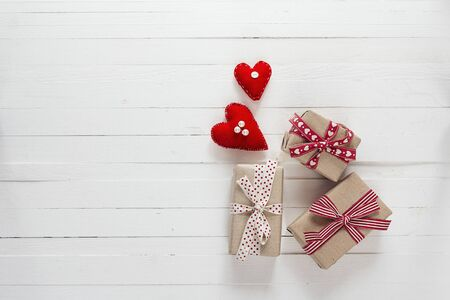 Background with gift boxes and hearts on white painted wooden planks. Place for text. Top view with copy space.