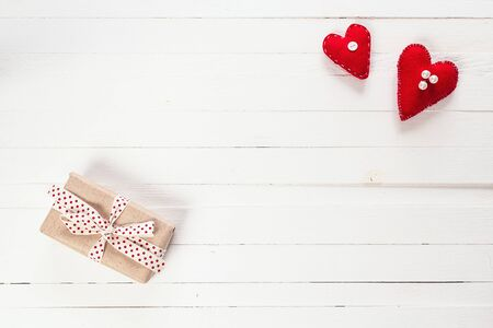 Background with gift box and hearts on white painted wooden planks. Place for text. Top view with copy space.