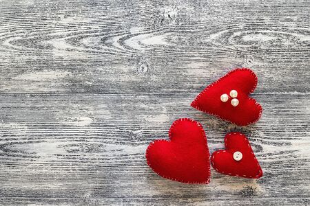 Background with three red hearts on grey wooden planks. Place for text.