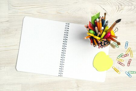 Back to school concept with blank open notebook and school supplies on light wooden table. Copy space, top view.