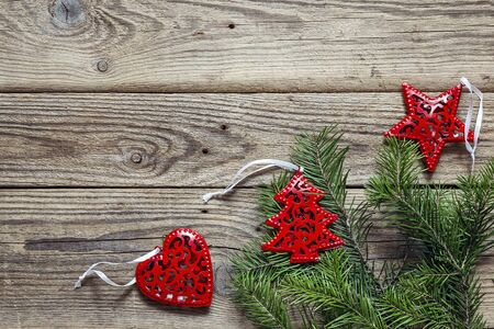 Background with fir branches and red Christmas decorations on old wooden boards. Space for text. Top view. Stock fotó