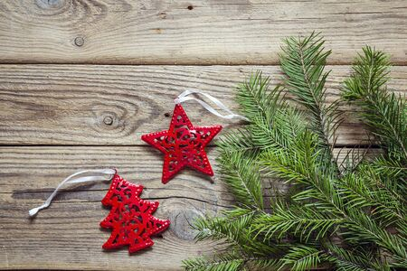 Background with fir branches and red Christmas decorations on old wooden boards. Space for text. Top view.