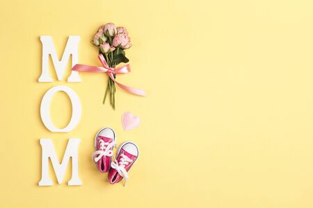 Word mom with pink baby girl sneakers and small bouquet of roses on a yellow background. Flat lay, top view, copy space. Imagens
