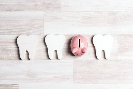Pink piggy bank with teeth on a light wooden background. Investing in dental health care. Stockfoto
