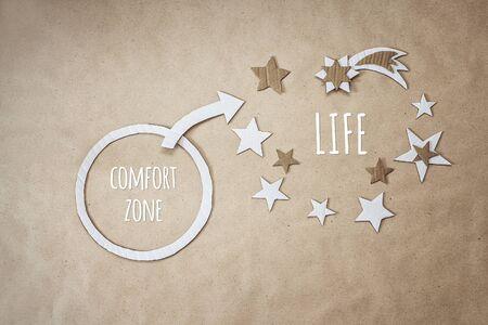 Cita inspiradora y aliento para salir de su zona de confort. La vida comienza al final de tu zona de confort. Modelo de cartón cortado a mano. Foto de archivo
