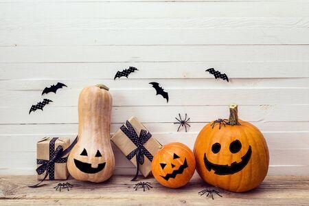 Tre zucche con facce dipinte, scatole regalo e ragni decorativi su un tavolo di legno su uno sfondo di lavagne bianche. Sfondo per Halloween. Spazio per il testo.