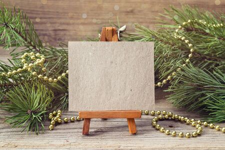 Miniature easel with blank card, pine branches and Christmas decorations. Space for text.