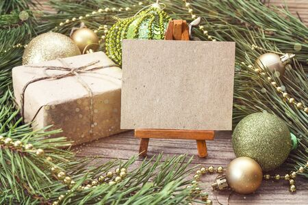 Miniature easel with blank card, gift box, pine branches and Christmas decorations. Space for text.