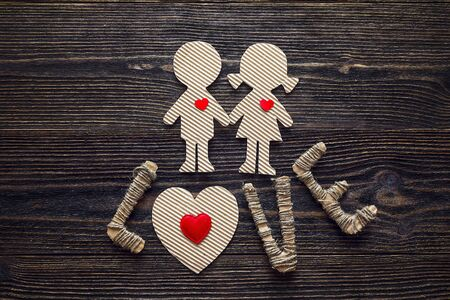 Cardboard silhouettes girl and boy with hearts and the word love on a wooden table. Valentine's Day background. Space for text. Top view.