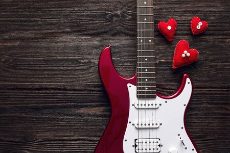 Red electric guitar with hearts on a dark wooden background. Valentine's Day background. Space for text. Top view. 免版税图像