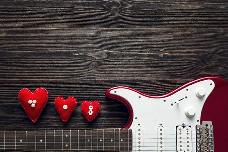 Red electric guitar with hearts on a dark wooden background. Valentine's Day background. Space for text. Top view.