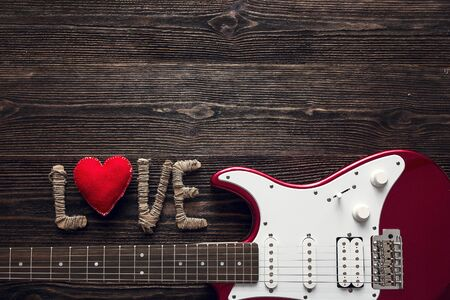 Red electric guitar with the word love and heart on a dark wooden background. Valentine's Day background. Space for text. Top view.