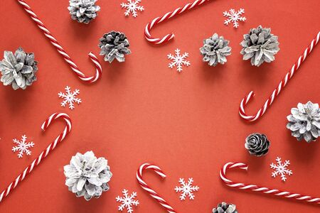 Red Christmas background with candy canes and pine cones. Top view, flat lay. Copy space for text.