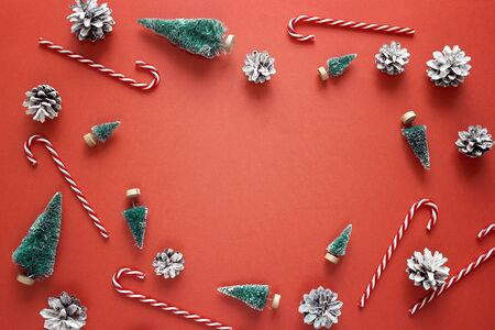 Red Christmas background with firs, candy canes and pine cones. Top view, flat lay. Copy space for text.