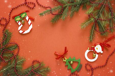 Red Christmas background with fir branches and decorations. Space for text. Top view.