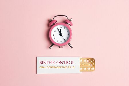 Female oral contraceptive pills blister with alarm clock on pink background. Women contraceptive hormonal birth control pills. Time reminder for taking pills. Standard-Bild