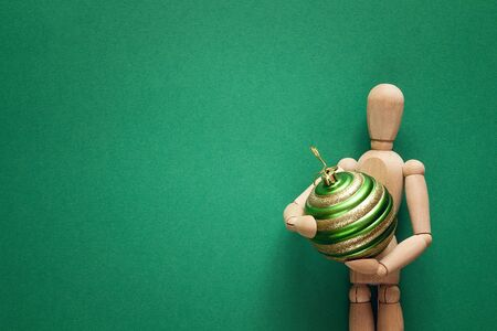 Classic wooden dummy holds Christmas ball on a green background. Space for text. Reklamní fotografie