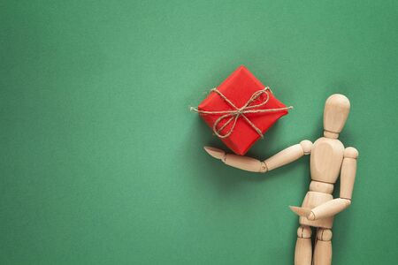 Classic wooden dummy holds Christmas gift on green background. Space for text. Reklamní fotografie