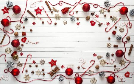 Christmas background with red decorations, sweets and space for text on white wooden boards.Top view, flat lay.
