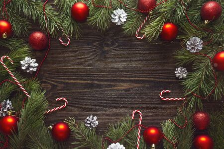 Christmas background with pine branches and red decorations on dark wooden boards. Space for text. Top view.